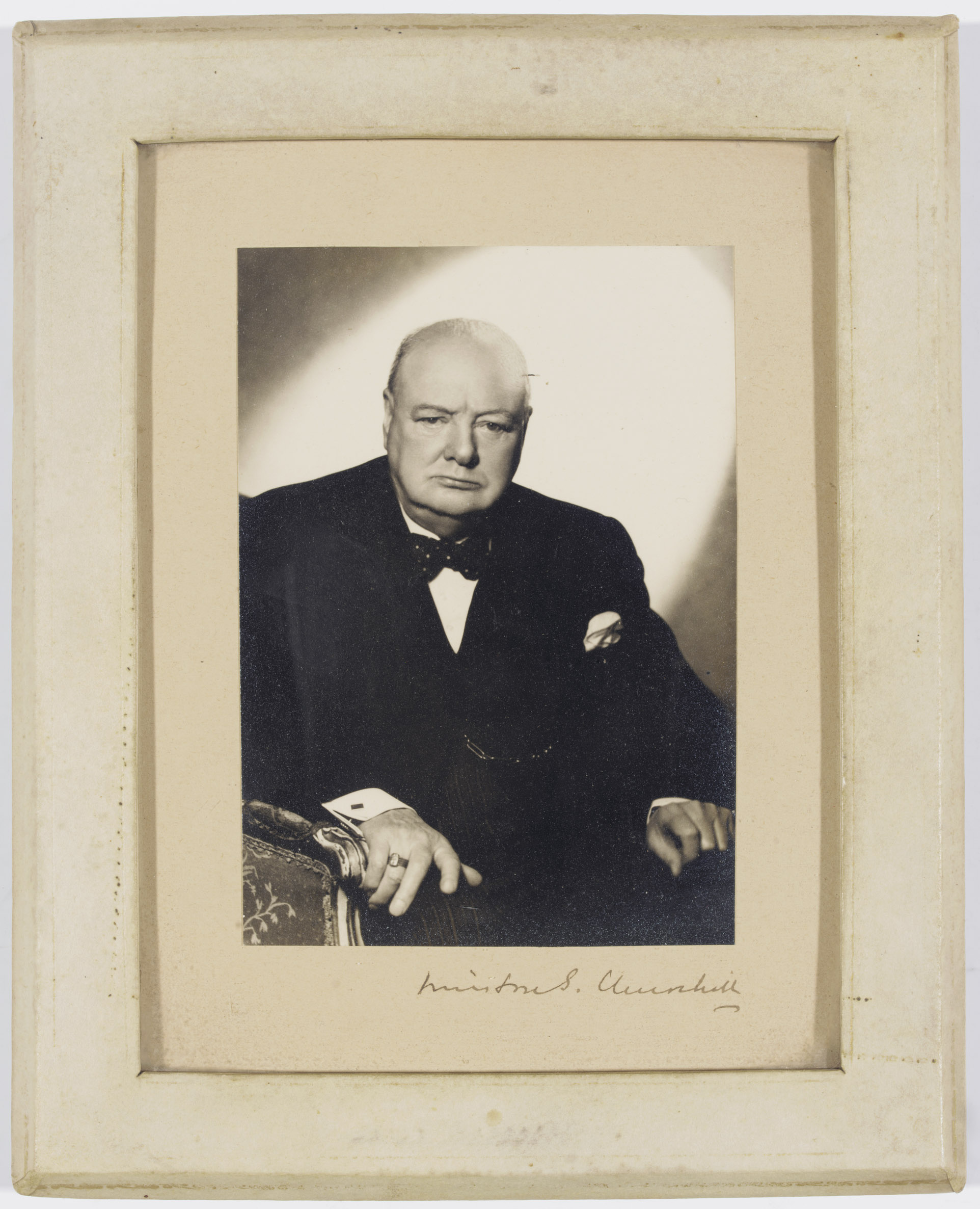 CHURCHILL, Winston S. (1874-1965). Photograph signed (on mount, 'Winston S. Churchill'), a half-length photograph [by Vivienne] showing Churchill seated, [c.1950], 152 x 108mm, laid down on card, 305 x 155mm, framed and glazed; with a photograph signed by Clementine CHURCHILL ('Clementine S. Churchill'), December 1953, 167 x 139mm, laid down on card, framed and glazed (the photographs not examined out of frames).